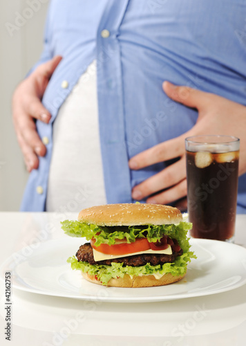 Fat man with hamburger and cola