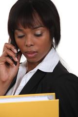 gorgeous black businesswoman on the phone holding folder