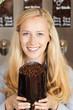 lächelnde verkäuferin mit einer tüte kaffeebohnen