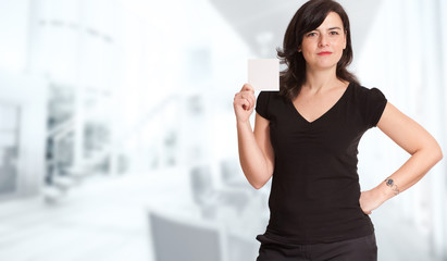 Attractive brunette in a corporate background holding a blank no