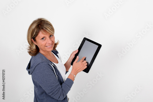 Senior woman pointing at electronic tablet screen