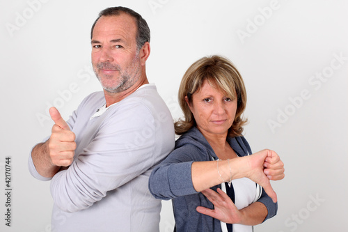 Senior couple with thumbs up and down