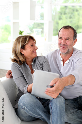 Senior married couple choosing movie on tv