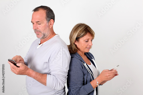 Senior couple sending short message with smartphone