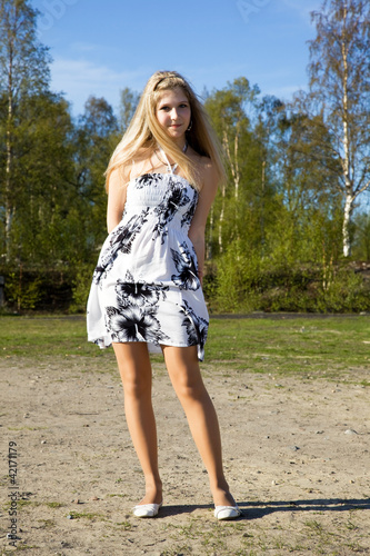A slender girl in a birch forest