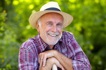 Happy senior gardener with straw hat