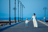 Happy woman and her little son on wooden jetty
