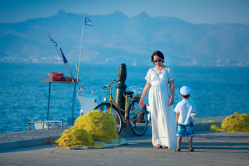 Woman and her son talking on jetty by the sea