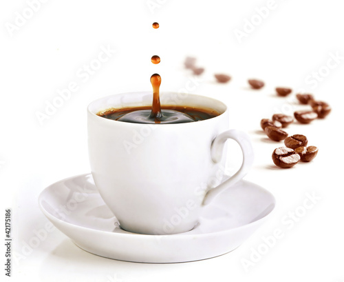 A cup of coffee with a splash of drops and coffee beans. - 42175186