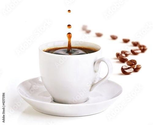 Filiżanka kawy z odrobiną kropli i ziaren kawy.