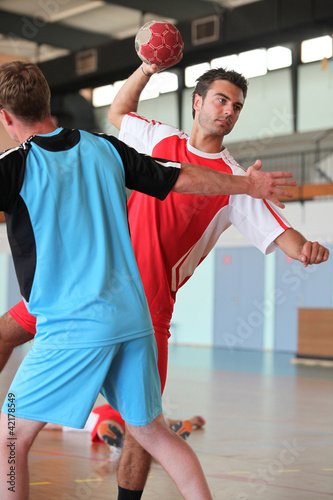 Man throwing ball during handball game