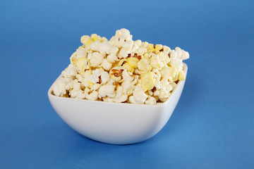 Delicious popcorn bowl on blue background