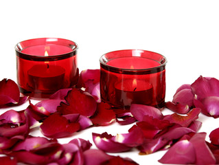 Red candle with rose petals