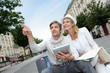 Couple visiting city with help of map and electronic tablet