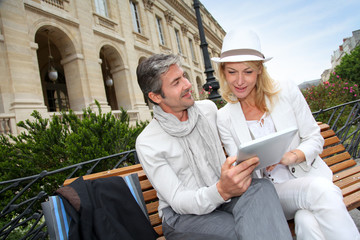 Trendy couple using electronic tablet on city bench