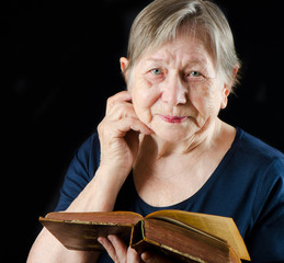 Elderly smiling woman with book
