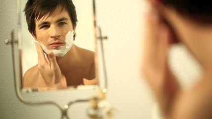 Young man shaving himself in front of a mirror