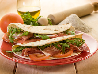 piadina with ham arugula and tomatoes, typical italian sandwich
