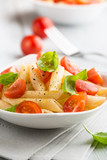 Pasta salad with cherry tomatoes and basil leaves