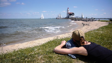 Girl watching lighthouse and sailing boat in sunny landscape