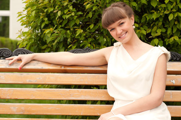 A beautiful woman is sitting on a park bench