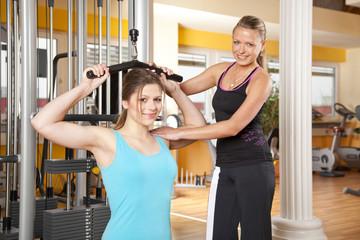 lächelnde junge Frau mit Trainerin trainiert ihren Latissimus