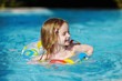 Pretty little girl swimming in a pool