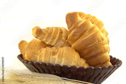 Croissants in a bread basket on white background