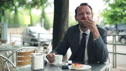 Young businessman eating breakfast in cafe by the street