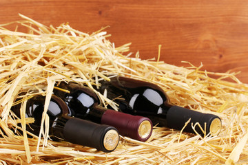 Bottles of great wine on hay on wooden background