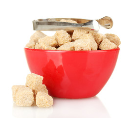 brown cane sugar cubes in bowl with sugar-tongs isolated