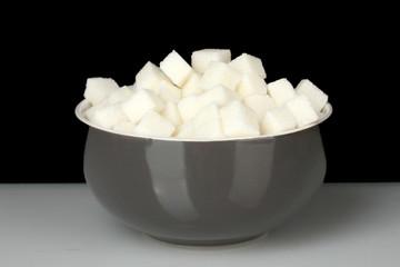 White lump sugar in bowl on black background