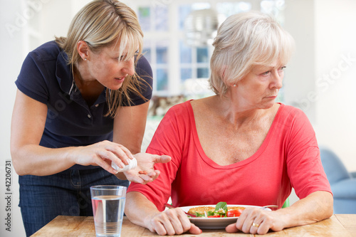 Older woman refusing medication at home