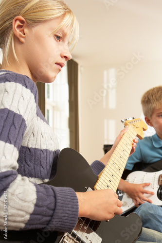 Boy and girl playing electric guitars at home