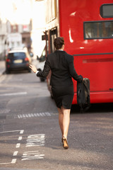 Businesswoman running for bus