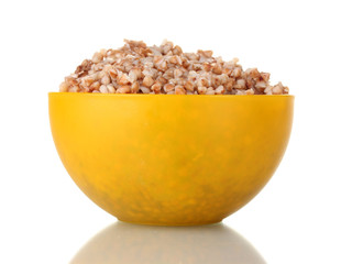 Boiled buckwheat in a yellow bowl isolated on white