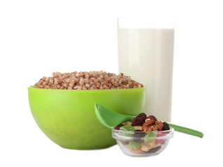 Boiled buckwheat in a green bowl a glass of milk isolated