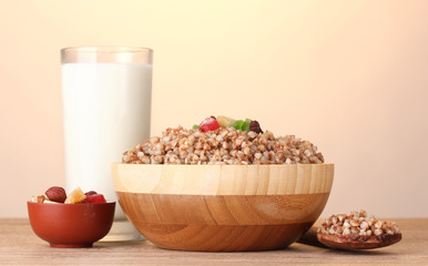 Boiled buckwheat in a wooden bowl with a glass of milk