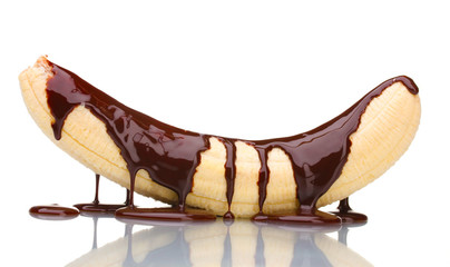 Banana poured with liquid chocolate isolated on white.