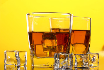 two glasses of scotch whiskey and ice on yellow background