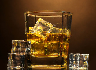 glass of scotch whiskey and ice on brown background
