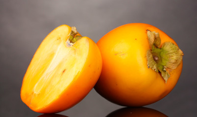 Appetizing persimmons on grey background