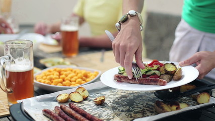Woman hands putting sausages on the plate