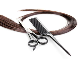 Shiny brown hair with hair cutting shears and comb isolated