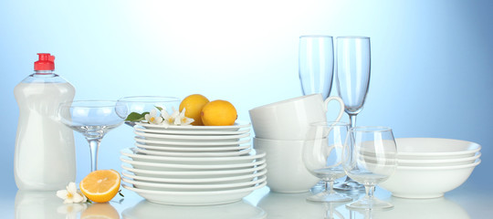 plates, glasses and cups with cleaning liquid on blue background