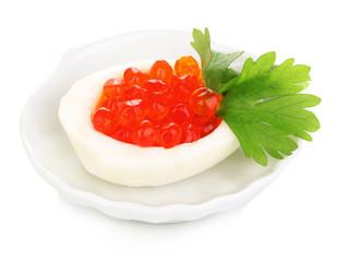 Red caviar in egg on little white saucer isolated on white