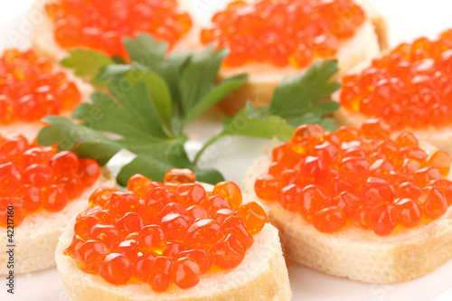 Red caviar on bread on white plate close-up
