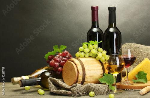 wine, cheese and grapes on wooden table on grey background