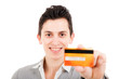 smiling young man showing credit card, isolated on white backgro