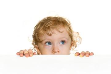 Kind blickt gespannt über die Tisch-Kante